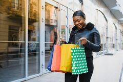 Free Young Black Woman Holding Shopping Bags Royalty Free Stock Images - 182143189