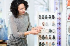 Young woman in jewellery store looking for wristwatches Royalty Free Stock Image
