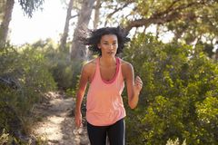 Young black woman jogging in a forest, close up Stock Photos
