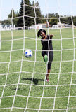 Young black woman kicking soccer ball into net Stock Photos