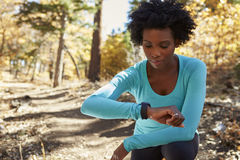 Young black woman kneeling in a forest checking smartwatch Royalty Free Stock Photos