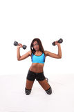 Young black woman on knees with dumbbells Royalty Free Stock Image
