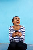 Young black woman laughing with cell phone against blue wall Stock Photography