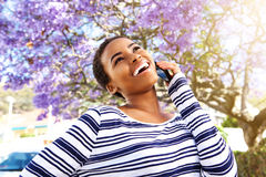 Young black woman laughing with cell phone outside Stock Photos