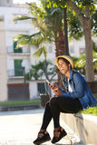 Young black woman laughing and listening to music on cell phone Stock Image
