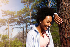 Young black woman leaning on tree trunk and smiling Royalty Free Stock Photography