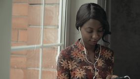 Young black woman listening music travelling looking outdoor the window, pensive - thoughtful, thinking future, music. Young black woman listening music looking stock video footage