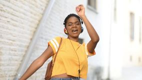 Young black woman listening to the music and dancing in the street. African female with very short hair in urban background stock footage