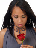 Young black woman looking down at red rose Stock Photos