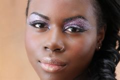 Young black woman looks at the camera. Beautiful black woman tight closeup with mermaid-like makeup; lavender sparkling eyes and pale sparkling lips Stock Photo
