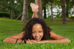Young black woman lying down on the grass Stock Photos