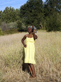 Young black woman outdoors in yellow dress. Young African American woman outdoors yellow dress and head scarf Stock Image