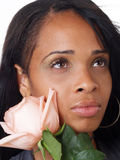 Young black woman with pink rose along cheek Stock Photos