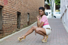 Young Black Woman Posing in Brick Alley. Beautiful sexy young Black Woman Posing in Brick Alley while squatting down.  Modeling fashion Stock Photo