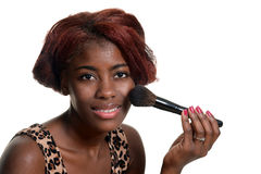 Young black woman putting on blush makeup Stock Photo