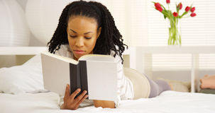 Young black woman reading on bed Royalty Free Stock Photo