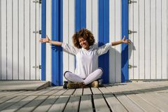 Young black woman on roller skates sitting near a beach hut. Girl with afro hairstyle rollerblading on sunny promenade Royalty Free Stock Photos