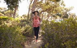 Young black woman running through a forest Royalty Free Stock Images