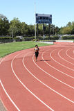 Young black woman running on track long shot Stock Photography