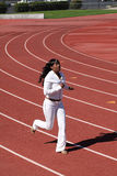 Young black woman running on track sweat suit Stock Photos