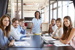 Young black woman and seated team at meeting facing camera Stock Image