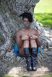 Young black woman sitting at base of tree Stock Photo