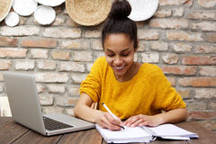 Young black woman sitting at cafe with laptop and notebook Stock Photography