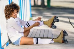 Young black woman sitting on wooden floor puts on skates. Royalty Free Stock Photography