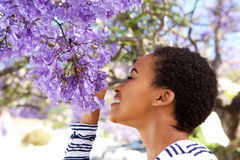 Young black woman smelling flowers on tree Royalty Free Stock Photo