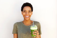 Young black woman smiling with fresh cup of fruit juice. Portrait of young black woman smiling with fresh cup of fruit juice against white wall Stock Images