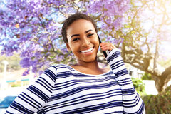 Young black woman smiling outside with cell phone Royalty Free Stock Photo