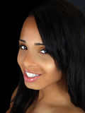 Young black woman smiling portrait. Smiling portrait of young black woman with dark background Royalty Free Stock Photo