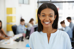 Young black woman smiling to camera in an open plan office Royalty Free Stock Images
