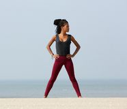 Young black woman standing at beach with hand on hips Royalty Free Stock Image