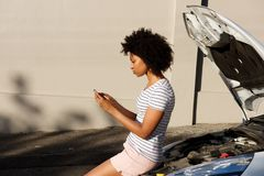 Young black woman standing by broken down car and using cell phone for assistance Stock Photos