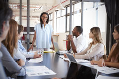 Young black woman stands addressing colleagues at meeting Stock Photos