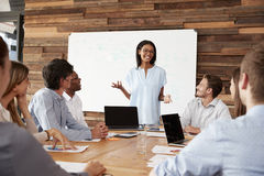 Young black woman stands addressing colleagues at a meeting royalty free stock photography