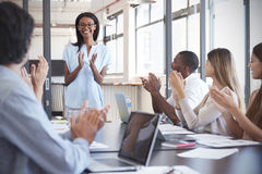 Young black woman stands clapping with colleagues at meeting Royalty Free Stock Photos