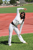 Young black woman stretching at track on grass Royalty Free Stock Photos