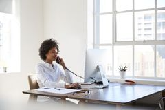 Young black woman talking on phone at her desk in an office royalty free stock photography
