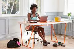 Young black woman using computer at home after exercising Royalty Free Stock Image