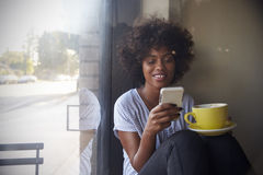 Young black woman using smartphone beside a window in a cafe royalty free stock photo