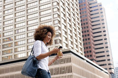 Young black woman walking and listening to music on city street. Portrait of young black woman walking and listening to music on city street Royalty Free Stock Images