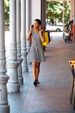 Young black woman walking with mobile phone and shopping bags Royalty Free Stock Images