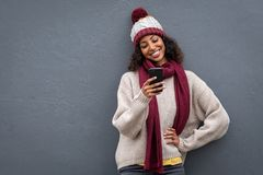 Young black woman in winter clothes using smartphone. Young african woman using mobile phone standing against grey wall. Smiling beautiful girl wearing warm royalty free stock photography