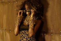 Free Young Black Woman With Afro Hair Wearing Gold Accessories And Makeup Putting On Sunglasses, Looking Away Stock Photos - 72499473