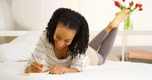 Young black woman writing in journal. On bed Royalty Free Stock Photos