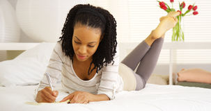Young black woman writing in journal. At home Royalty Free Stock Photos