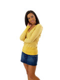 Young black woman in yellow sweater and jean skirt. Young woman standing in yellow top and jean skirt Stock Photo