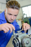 Young blacksmith fixing machine part Stock Photo